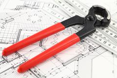 Pliers, and architectural plan of the modern house - stock photo
