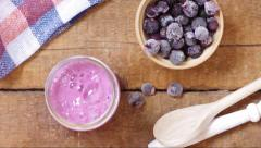 Pour currant smoothie in a glass cup from the blender on a wooden board Stock Footage