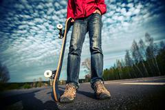 Rider standing on the asphalt road and holding skate board over the blue sky  Stock Photos