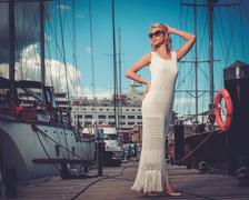Stylish wealthy woman on a wooden pier - stock photo