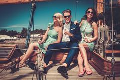 Stylish wealthy friends having fun on a luxury yacht Stock Photos