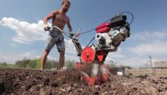 Strong athlete man working in the field with ripper cultivator Stock Footage