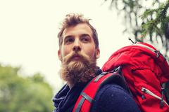 man with beard and backpack hiking - stock photo