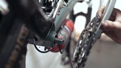 Professional mechanic setting up crankset on bicycle in workshop. Bike repair Stock Footage