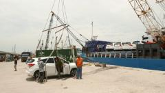 Worker come out of car before vehicle lifted up on ship deck Stock Footage