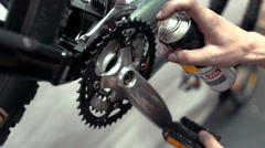 Spraying and cleaning crank arms in workshop. Bike repair - stock footage
