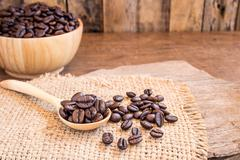 Roasted coffee beans in a wooden spoon - stock photo