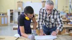 Carpenter with apprentice in training period - stock footage
