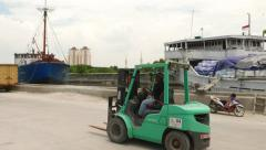 Forklift drive along dusty road in old port, tracking shot. Stock Footage