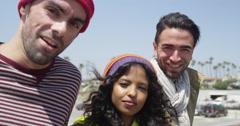 Three hip ethnic diverse friends staring at camera panning at the beach - stock footage