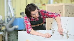 Young woman in carpentry training assembling furniture - stock footage