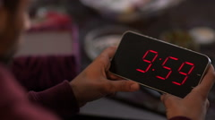 Man holding a digital clock and looking at the time that elapses in it - stock footage