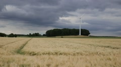 Rural Wheat Field and thunderstorm with wind turbine Stock Footage