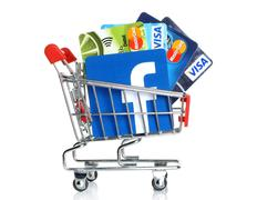 Facebook logo into shopping cart with cards Visa and MasterCard - stock photo
