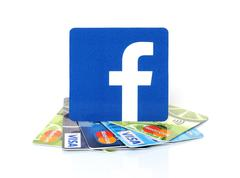 Facebook logo on cards Visa and MasterCard on white background - stock photo