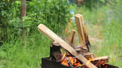 Wood burns in the grill outdoors, preparing firewood for cooking meat Stock Footage