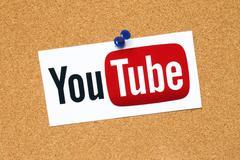 YouTube logotype pinned on cork bulletin board - stock photo