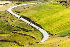 High Altitude Road In Ecuador Crossing Agricultural Landscape - stock photo