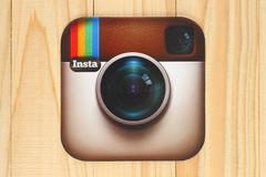 Instagram logotype camera printed on paper and placed on wooden background Stock Photos
