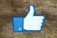 Facebook thumbs up sign printed on paper and placed on wooden background Stock Photos