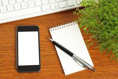 Smart phone, keyboard, notepad, pen and green plant on wooden background Stock Photos