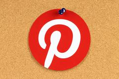 Pinterest logotype printed on paper and pinned on cork bulletin board - stock photo