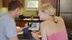 Young couple video chatting with parents on tablet online Stock Footage