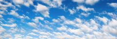 Fluffy white clouds on blue sky panorama - stock photo