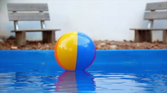 Colorful beach balls floating in pool in slow motion Stock Footage