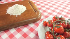 Ingredients to prepare pizza on a white red square tablecloth dolly shot Stock Footage