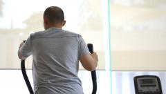 Man exercising elliptical treadmill trainer Stock Footage