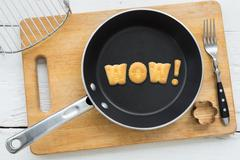 Cookie biscuits word WOW in frying pan - stock photo