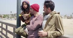 Cool hipster friends enjoying a mellow spring break on a pier Stock Footage
