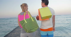 Friendly young couple walking on the pier after shopping Stock Footage