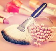 Powder and brush for makeup on the table. Vintage retro hipster style version Stock Photos