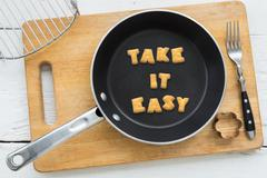 Cookie biscuits quote TAKE IT EASY in frying pan - stock photo