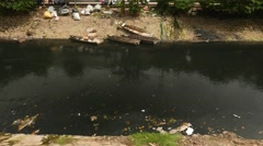 Black water polluted by fuel oil, trash float, small boats Stock Footage