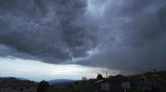 Rain clouds moving quickly over mountain village-timelapse Stock Footage