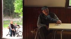 Children monitor elderly man smoking a cigarette in rural Room Stock Footage
