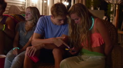 Friends Hang Out At Summer Pool Party, Couple Looks At Smart Phone Together (4K) Stock Footage