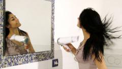 Happy girl blow drying long black hair in front of mirror in bathroom slow mo Stock Footage