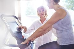 Physical therapy guiding woman on stationary bike Stock Photos