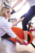 Physical therapist guiding woman's leg on stationary bike - stock photo