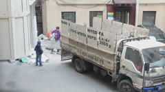 Manual workers load construction debris in small truck body. Recycling rubbish Stock Footage