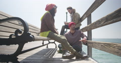Stock Video Footage of Group of young multiracial adults on pier together calm on bright sunny day