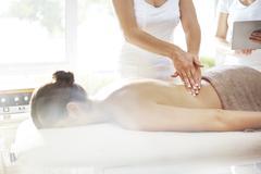 Masseuse massaging woman's back Stock Photos