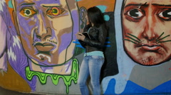 Happy young woman taking notes near a wall with murals Stock Footage