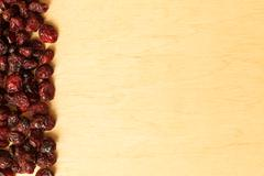 Border frame of dried cranberries on wooden background Stock Photos
