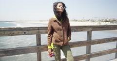 Beautiful young black woman absorbing the cool sea breeze from the pier Stock Footage