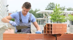 Young brick layer working outside on brick wall construction Stock Footage